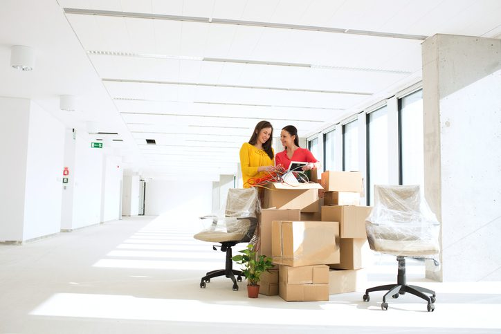 two women unpacking boxes in new office
