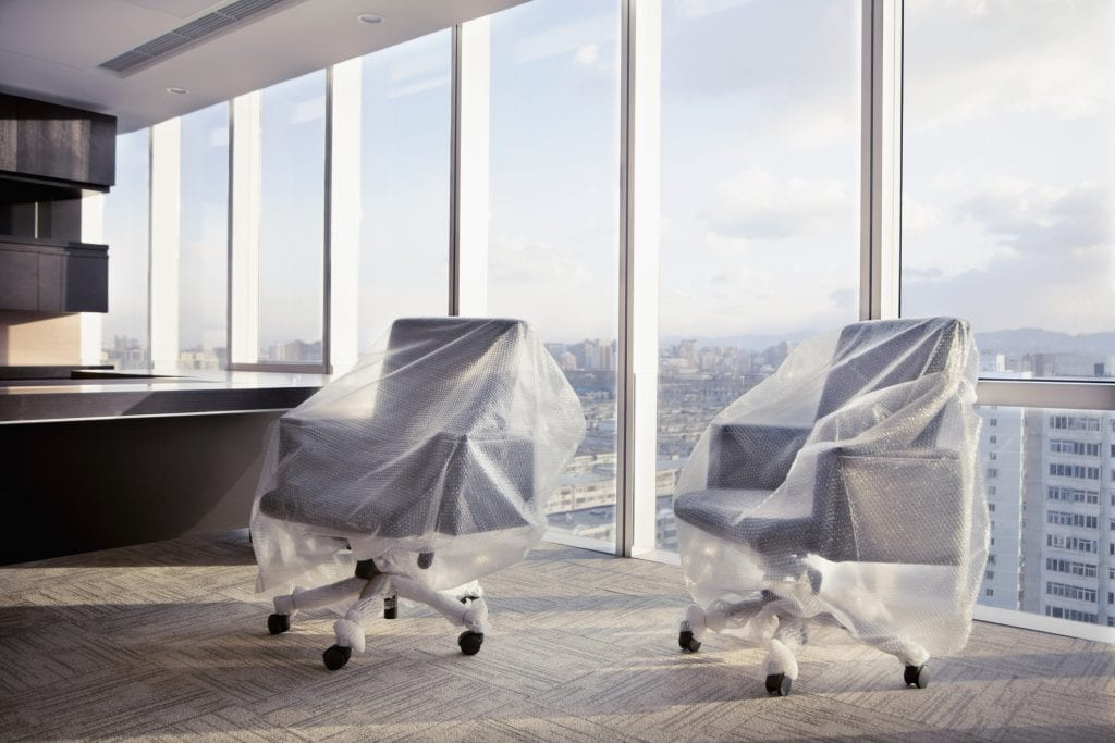 Desk chairs wrapped with bubble wrap in executive office