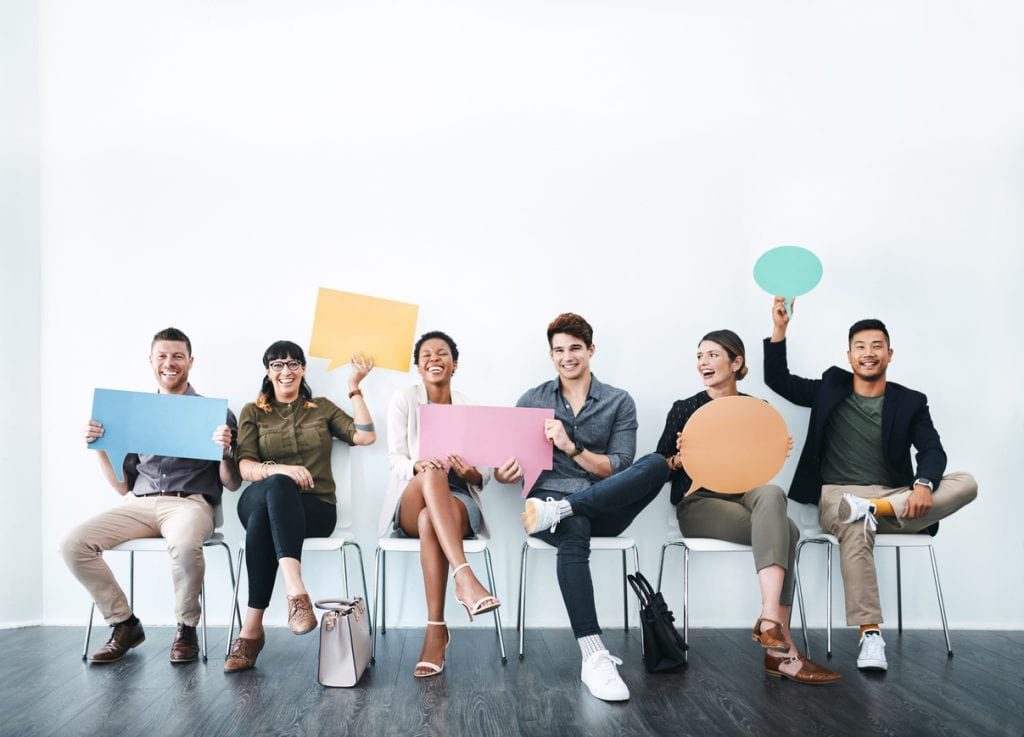 Business people holding up speech bubbles