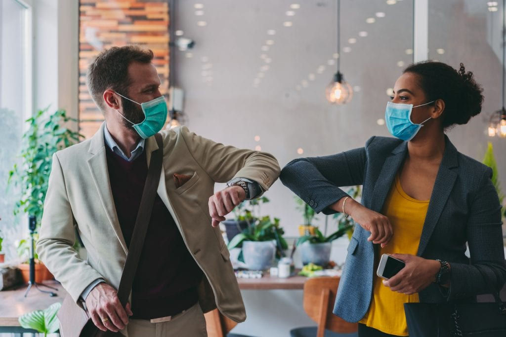 Employees greeting each other with masks during COVID
