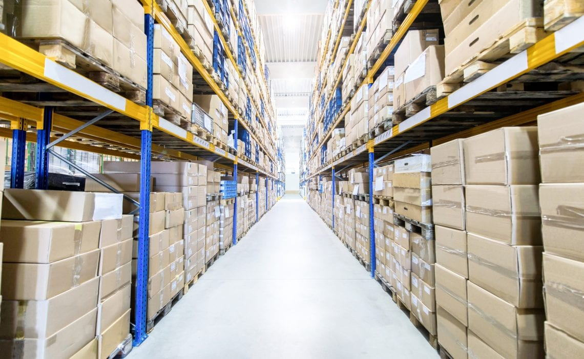Horizontal color image of large distribution storage with racks full of packages, boxes, pallets, crates ready to be delivered. Logistics, freight, shipping, receiving.